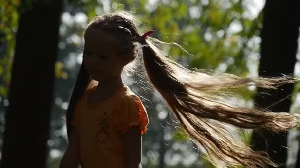 Girl is Turning Around at The Sun Smiling Slow Motion Little Girl With Long Fair Hairs Two Ponytails Lilac Bows T-Shirt Girl at Playground Tilt Down