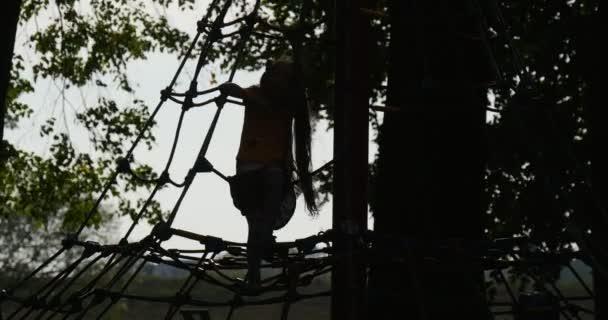 Ragazza della siluetta della ragazza è arrampicata per le sagome di alberi scale di corda bambina con lunghi peli due code di cavallo ragazza sta giocando al parco giochi