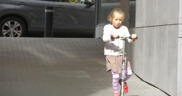 Dívka na Kick Scooter přístupů The fotoaparát dívky v sukni s blond vlasy je s úsměvem zbavit koloběžka na ulici Walking lidem auta