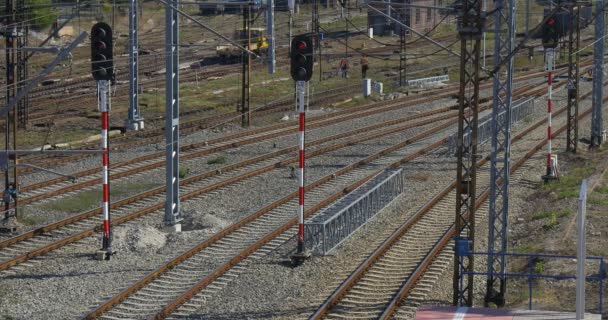Žlutá lokomotiva vzdáleně lokomotiva je že nechat dva dělníci jsou pěší přes železniční železniční stanice železniční křižovatka železniční semafor