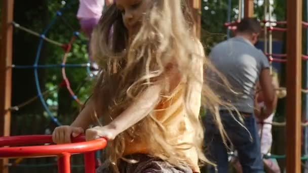 Girl is Swinging on a Swing With Her Toy Rabbit Pink Tilda Swinging on a Swing Little Girl With Long Fair Hairs in Orange T-Shirt at the Playground
