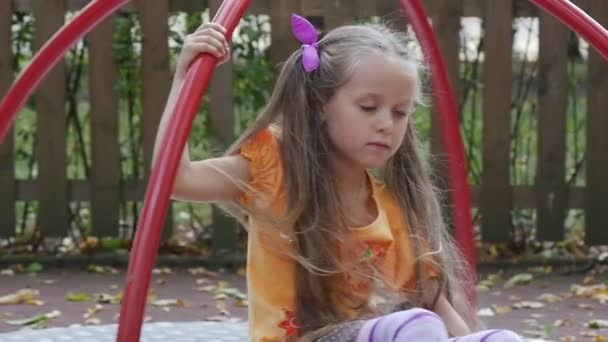 Girl is Swinging on Carousel with Toy Rabbit Pink Tilda Little Girl With Long Fair Hairs in Orange T-Shirt is Playing Outdoors at the Playground Sunny