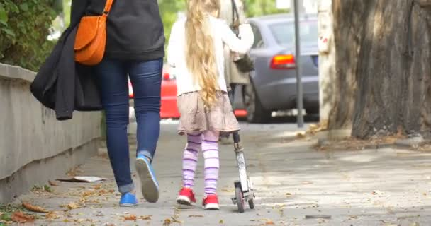 Mom Little Blonde Girl is Riding The Kick Scooter by Street Woman Mom is Walking along Girl Daughter Orange Bag People are Walking Away Parked Cars