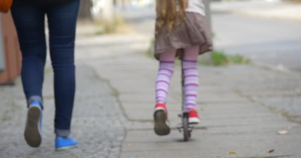 Little Blonde Girl is Riding The Kick Scooter by Street Red Sneakers Close Up Tilt Up Woman Mom is Walking along Girl Daughter People are Walking Away