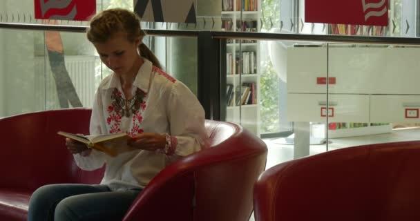 Nő a piros kanapén ül és olvas a könyv, akkor ő bezárja a könyv Feláll és megy el John Paul Ii városi Közkönyvtár Opole, Lengyelország