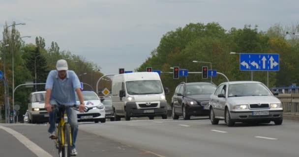 Dva muži na jízdní kola různých vozů přejeti zpevněné silnice Auto dopravní značení, dopravní značení a osvětlení Crossroad panoráma zamračený podzimní den Opole Polsko
