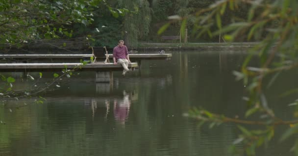 Man With Backpack Comes to Wooden Pier at The Lake River Deck Chair Man Has Took His Backpack Off Sits on Pier Floor with His Legs Down to Water Ducks