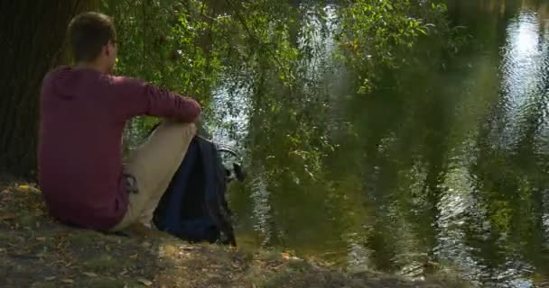 Man With Backpack Comes to River Bank Sits to The Ground Takes the Backpack Off Stands Up Goes Away Tourist Freelance Programmer Designer Rippling Water
