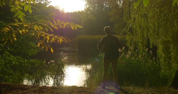 Mann mit Rucksack Silhouette kommt auf Fuß Took seinen Rucksack aus Sitzt auf Lake Bank mit Laptop freelance Programmierer Designer Texter Buchhalter