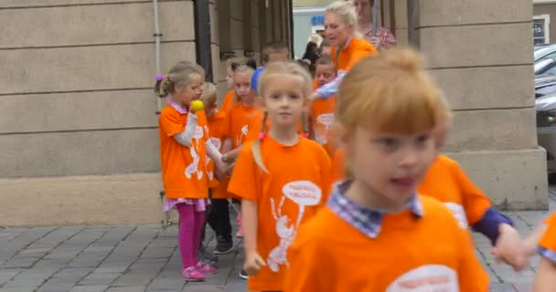Educators Are Standing And Looking after Walking Children Leading The Group of Children in Orange Yellow T-Shirts Walking by Street Toward Camera
