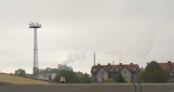 Kouř z továrny trubky prostředí znečištění továrních budov červená střecha domu průmyslové budovy bytový dům šedé nebe zelené stromy