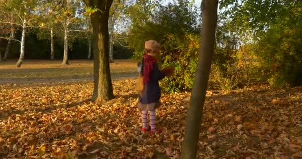 Dívka vybírá listí pro její kytici a hází malou holčičku s blonďatou Braid v Beret červený šátek a sako je procházka parkem