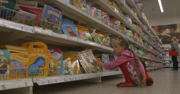 Baby Girl in a Supermarket Choose Book Reads a book, turning the pages