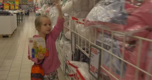 Little Girl Walks Briskly Through the Hall Supermarket. Girl Holds in Hands of Buying.