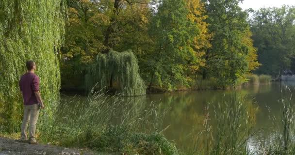Muž v brýle přijde na břehu jezera a sedí na zemi člověka je pozorování přírody stromy a zelené Reed jsou kolem žluté listí na stromech