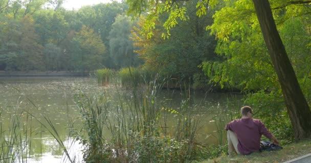 Muž v brýlích je, že sedí zadek v jezeře bance v lese při pohledu na vodu bere knihu od člověka, batoh je čtení knihy pod zelenou akátu