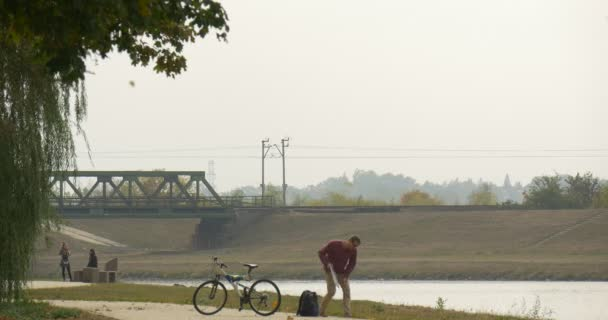 Man Took The Laptop From His Backpack Sits Down to the Ground at River in Park Working with Laptop Programmer Designer Copywriter Freelancer Bicycle