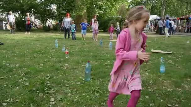 Girl Play Game Run Around The Bottles On The Grass