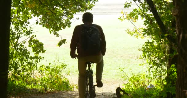 Man Rides Down On The Bicycle Frome The Hill To The Lawn Back View Man IN Beige Pants And Maroon Shirt With Backpack On His Back Sunny Autumn Day