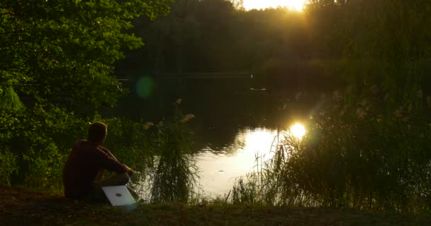 Man Sits On The Ground And Looks At The Lake He Takes Laptop And Begins To Work Programmer Copywriter Accountant Designer Freelancer Sunset Lakeshore