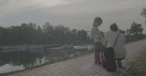 Little Blonde Girl With Braid is Standing Swaying with Her Beg And Talking to Her Mom Woman in White Sweater Family in Park Alley at the River