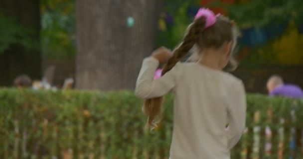 Little Blonde Girl is Walking in Park by Yellow Dry Leaves Holding Small Silver Bag Sits Stands Up Again People Men Women And Kids at Playground