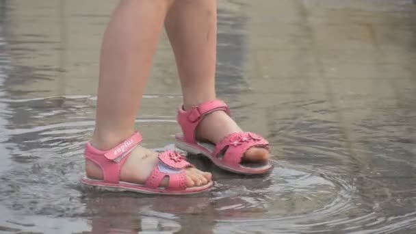 Two Little Girl Dressed in Pink Dress in Pink Sandals is Jumping in the Puddle Slow Motion
