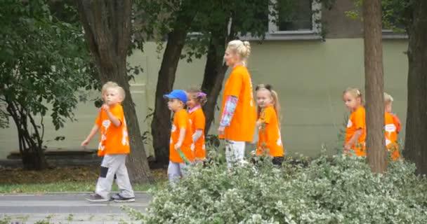 Orange T-shirt van gyaloglás, a tanár a Street tanárok szülők gyerekek vezető mentén ház emberek gyermekei: utcai nappali