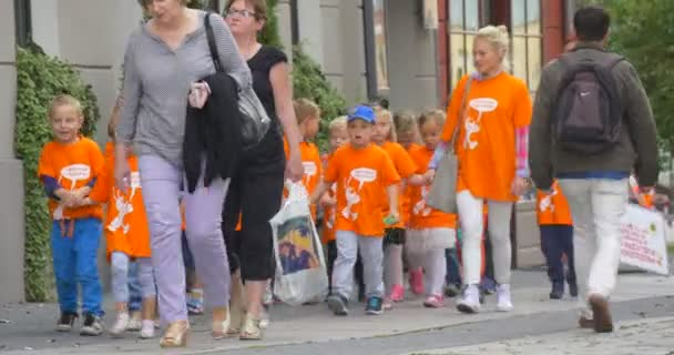 Kids in Orange T-Shirts Are Walking With Their Teacher by the Street Teachers Parents are Leading the Children Toward Camera Cars are Moving Daytime