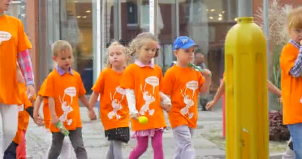 Kids in Orange T-Shirts are Walking with their Teacher by the Street Teachers Parents are Leading the Children Cars are Moving Shops Windows Daytime