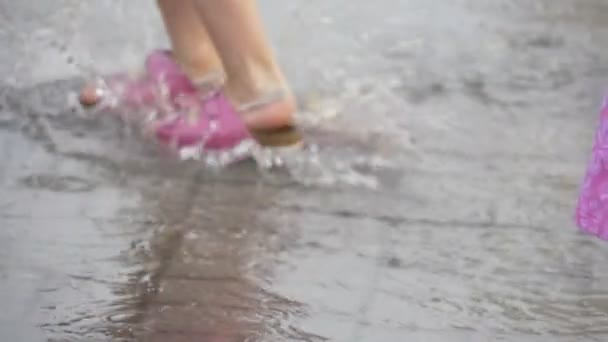 Two Little Girls Cheerfully Jumping Through The Puddles