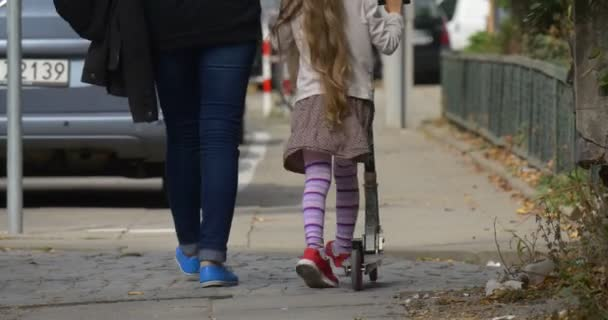 Mom Little Blonde Girl is Riding Kick Scooter by Street Feet Red Sneakers Blue Shoes Close Up Woman Mom is Walking along Girl Daughter Walking Away