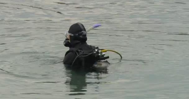 Člověk, který potápěč je stojí na jeho krk ve vodě začne plavat potápěči v plavky černé obleky pro dýchací přístroj jsou potápění do rybníka jezero řeky venku