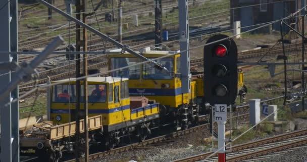 Žlutá lokomotiva se pohybuje daleko Raildoad vlaky vozy železniční železniční stanice železniční křižovatka železniční dopravní světla červené světlo drátu věže