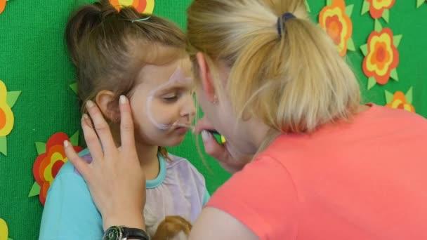 Pedagógus fiatal szőke nő festészet az arcát egy kicsit szőke lány festés a macska orra a lány arc által ecset óvoda osztályteremben