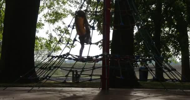Ragazza è arrampicata per la corda scale ragazza Silhouette ragazza piccola con lunghi peli Fair in maglietta arancione è giocare ai tronchi degli alberi parco giochi per bambini
