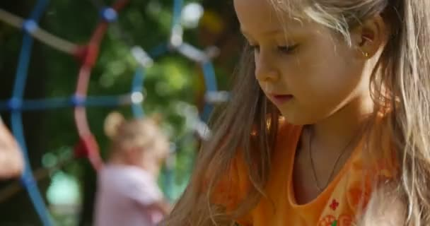 Little Girl With Long Fair Hairs in Orange T-Shirt is Jumping Playing Outdoors at Playground Prents with Child on Background Blurred Sunny Green Trees