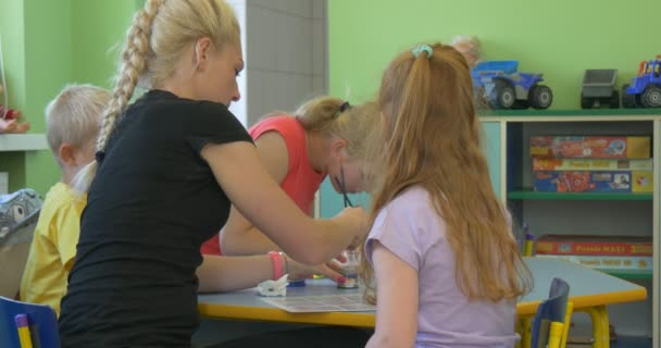 Group of Happy Children are Sitting at the Table with Teacher Young Blonde Woman and Painting with Brushes in Classroom of Kindergarten Talking