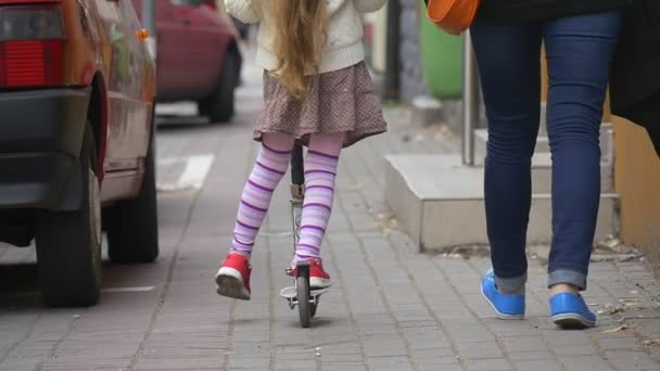 Girl on a Kick Scooter Girl in Skirt With Blonde Hairs is Ridding a Kick Scooter at the Street Girls Back Walking People Woman Mom Cars Slow Motion