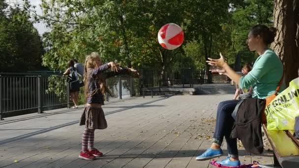 Dívka s dlouhou spravedlivé chloupky je hrací míč hodí míč do Mom chytí míč dívka je spuštěna následující Ball Park lidí na plot Sunny