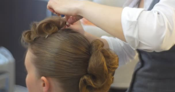 Stylist Hairdresser is Making The Hairstyle Curls by Curling Irons For a Woman with Long Brown Hairs Barbershop Hairdressing Salon Beauty Salon