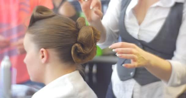Stylist fodrász teszi a frizura rögzítése a Curles egy nő, hosszú barna szőrszálakat Barbershop fodrászati szalon szépségszalon