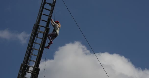 Girl Child is Hanging On Tether Climbing by The Rope Stairs Training of Saving Children from the High Builidings Down Up Blue Sky Fire Truck Tower