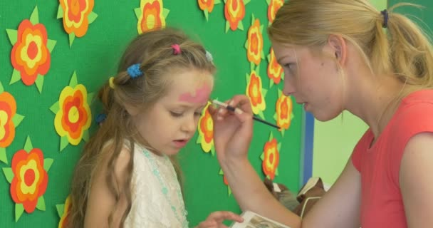 Educator Young Blonde Woman is Painting The Face of a Little Blonde Girl Painting the Pink Crown on Girls Forehead by Brush in Kindergarten Decor