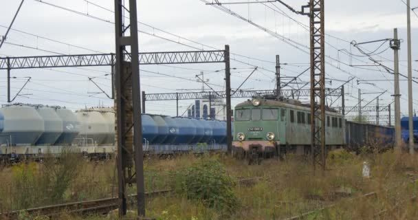 Cargo Train Stands On The Farther Railroad Track Green Electric Locomotive Pulls Long Freight Train Grey And Blue Freight Wagons Cloudy Autumn Day
