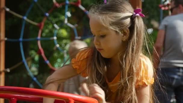 Dívka je Swaying s její hračka králík růžový Tilda visuté na Swing dívka s dlouhou spravedlivé chloupky v oranžové tričko se hraje na hřišti