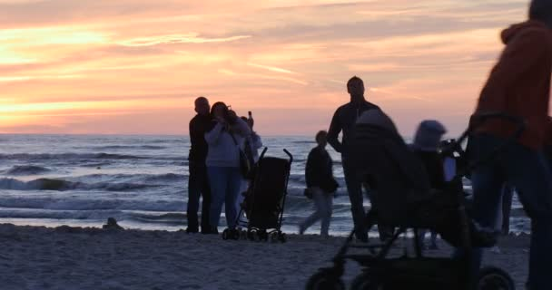 Lidé siluety rodin děti dítě v kočárku jsou vyhledávány na létající draci Walking v Sandy Beach vlny moře žluté slunce Kite Festival Leba