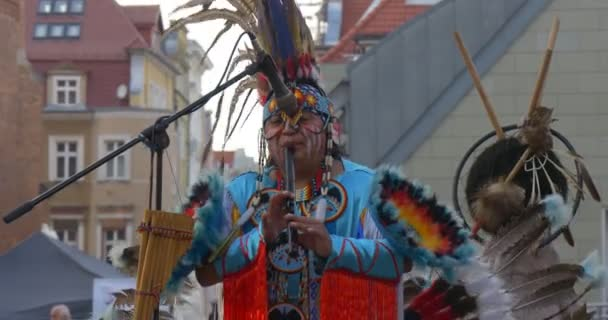 Man Playing Flute And Dancing Indians Performers in National Costumes Feathers Ribbons Necklaces are Singing Playing National Music Man Viewer Sitting