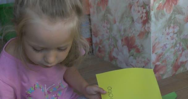 Holčička s plavými vlasy, růžové tričko a šedé kalhoty, sedí na podlaze, vyřezávání kruhů ze žluté listy papíru