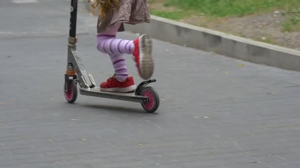 Little Blonde Girl Red Sneakers Close Up Tilt Up Girl is Riding The Kick Scooter Upward by Hill Sity Street Road Sign Parking Parked Cars Slow Motion